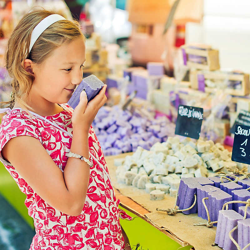 child sniffing soap at a market