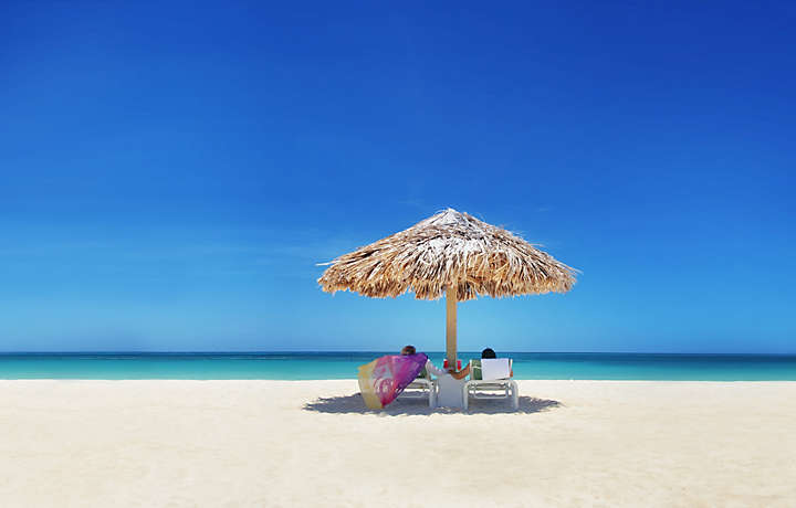 Couple relaxing under a Palapa in Aruba