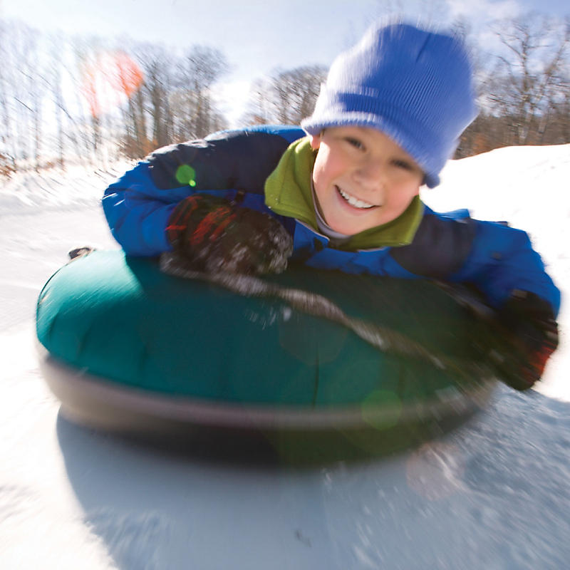 Boy snow tubing down hill at Loon Mountain