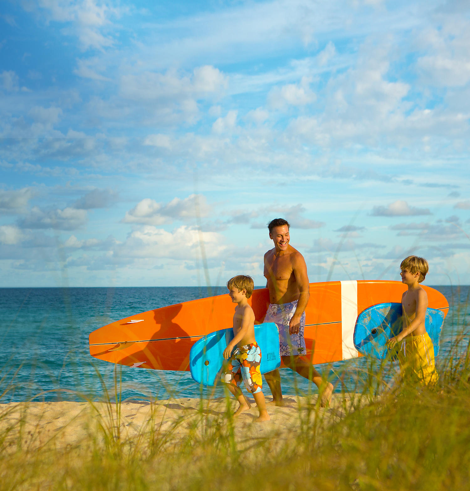 Father and his children holding surf boards heading towards the ocean.