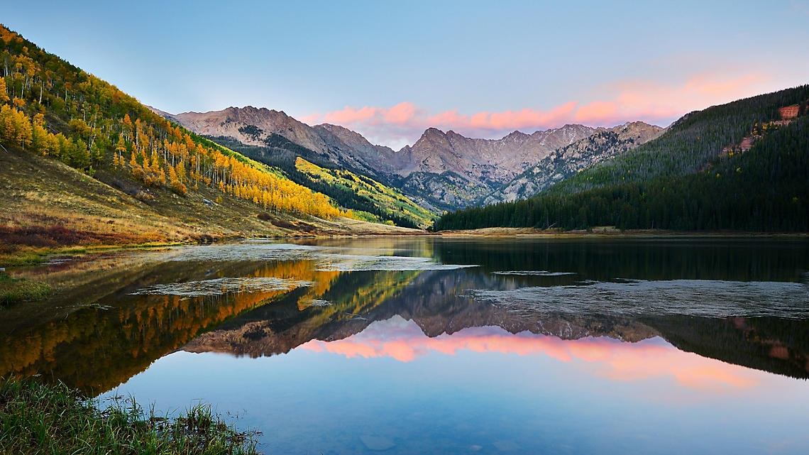 Placid lakes reflect valley vistas of cool aspen and pine