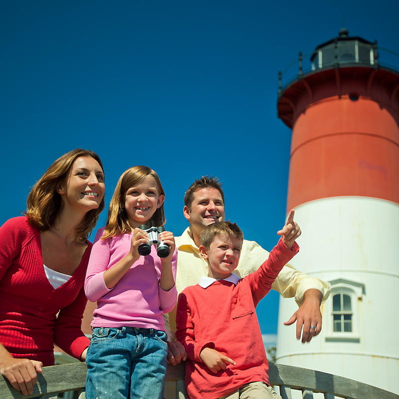 Family taking pictures outside of lighthouse