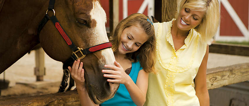 Mother and daughter bonding with a horse in the Ozarks