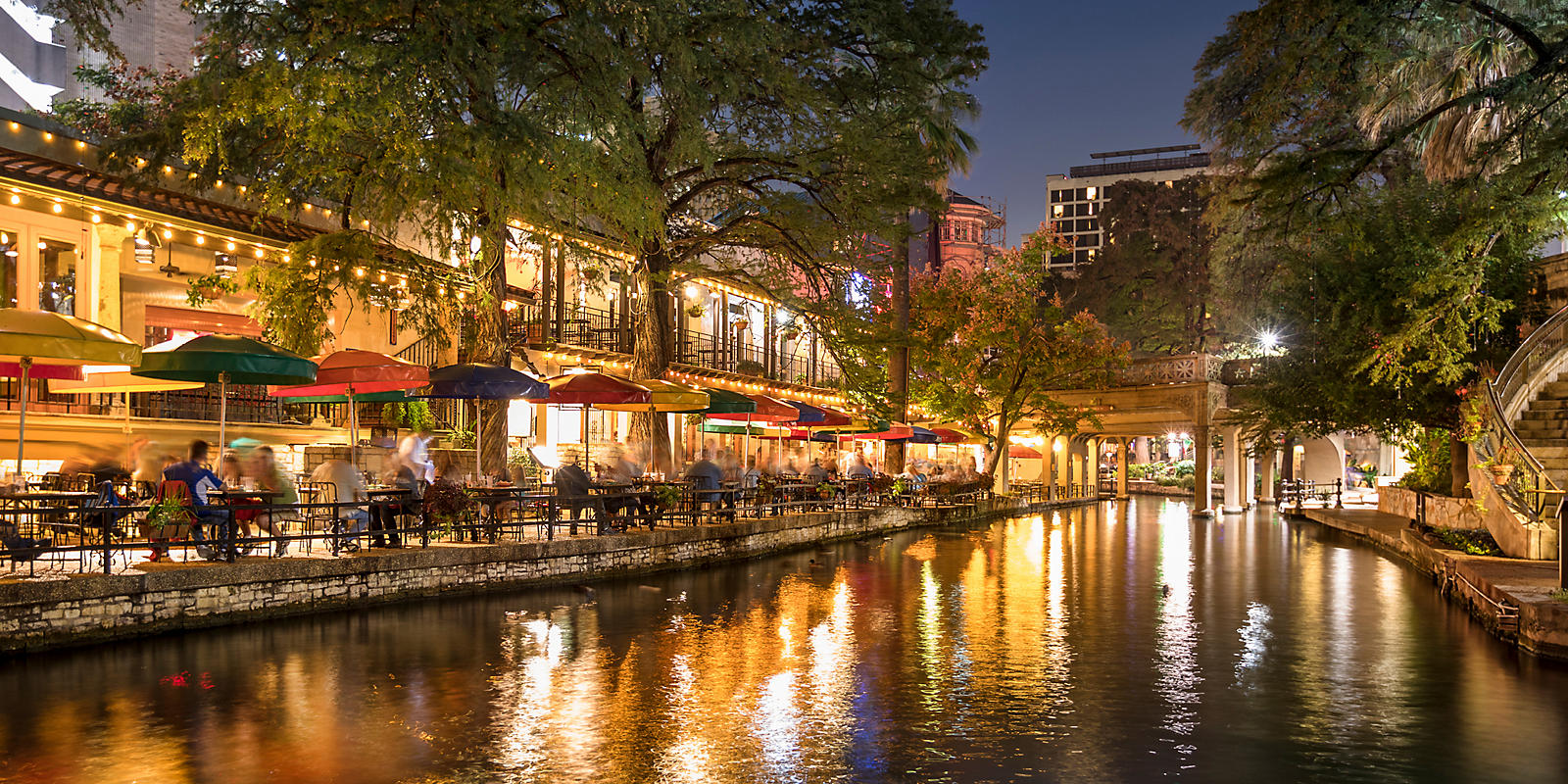 people dining at River Walk along the river at night
