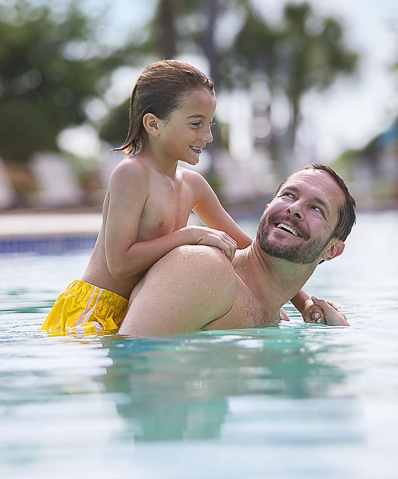 Father and son swimming in the pool.