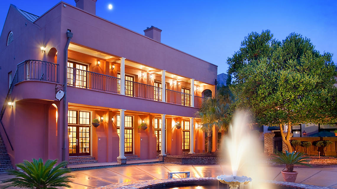 The Lodge Alley Inn exterior and fountain at dusk