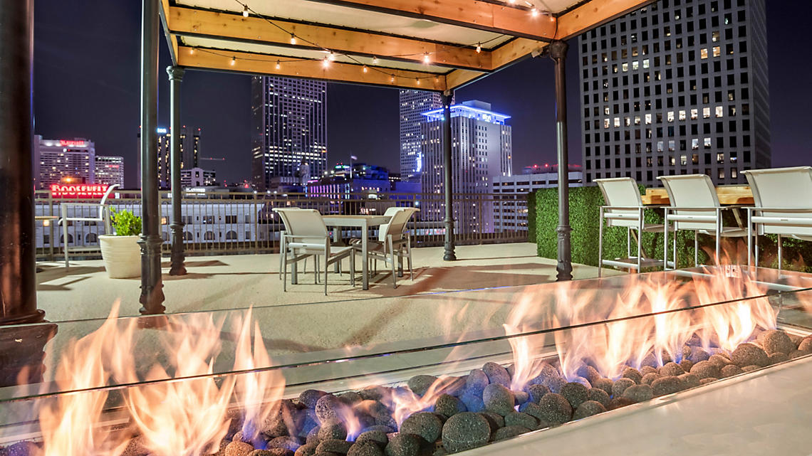 The rooftop deck offers a welcoming fire pit and seating areas for day and night city views.