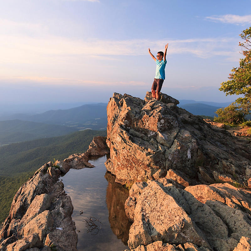 Man with hands up on top of cliff in Shenandoah National Park