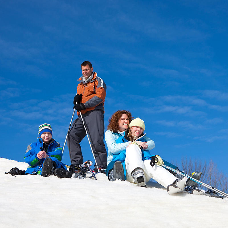 Man standing and lady and kids sitting on snow with skis