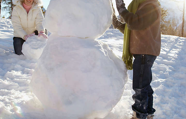 Mother and son building a snowman in Montana
